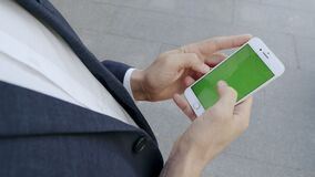 Businessman browsing internet on phone outside. professional using cellphone