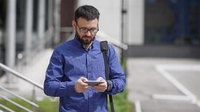 Businessman browsing smartphone. Adult businessman standing in street and browsing or typing smartphone. Adult businessman standing in street and browsing or stock video footage