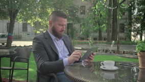 Businessman browsing tablet during coffe break. Outdoor. Steadicam shot. He is young and has beard. He is dressed on shirt and. Jacket. At backgroung there is stock video