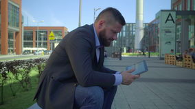 Businessman browsing tablet. He is sitting on the wall during break of the work. He is young and has beard. Man is dressed in suit and shirt. It is steadicam stock video footage