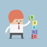 Businessman is building BRAND word, Brand building concept Stock Images