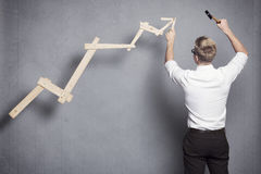 Businessman building business graph. Concept: Building your own career or business. Young businessman installing upward arrow on floating business graph with Stock Image