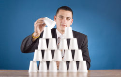 Businessman building cups' pyramid Stock Image