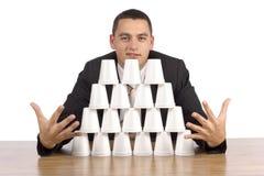 Businessman building cups' pyramid