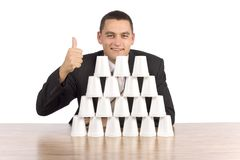 Businessman building cups' pyramid Royalty Free Stock Images