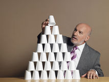 Businessman Building Pyramid Of Cups On Table Stock Photography