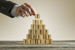 Businessman building a pyramid of wood blocks with people silhou Royalty Free Stock Image