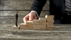 Businessman building a staircase for another entrepreneur to cli Royalty Free Stock Photos