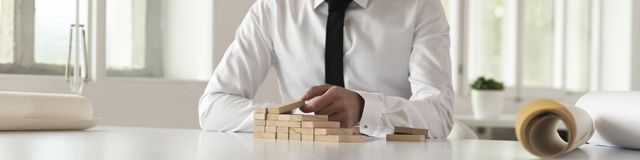 Businessman building steps of wooden blocks. Businessman seated at a table building steps of wooden blocks in a wide panorama view of his hands across the Stock Photos