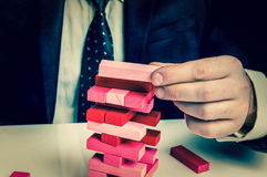 Businessman builds big tower with jenga bricks - retro style Stock Images