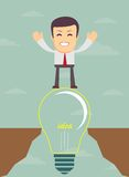Businessman on a bulb cross an abyss Stock Photo