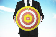 Businessman with bull's-eye and arrow at blue sky background Royalty Free Stock Photos