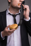Businessman with burger. Stock Image