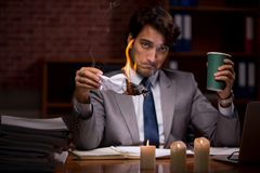 The businessman burning the evidence late in office. Businessman burning the evidence late in office stock images