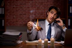 The businessman burning the evidence late in office. Businessman burning the evidence late in office stock photo