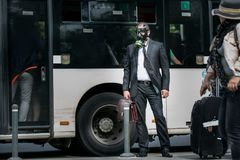 Businessman in a bus station wearing a gas mask. On the face Royalty Free Stock Images