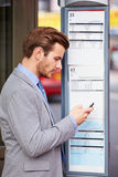 Businessman At Bus Stop With Mobile Phone Reading Timetable Stock Image