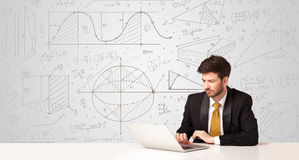 Businessman with business calculations background. Business man sitting at white table with hand drawn calculations background Stock Photo