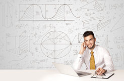 Businessman with business calculations background. Business man sitting at white table with hand drawn calculations background Royalty Free Stock Photography