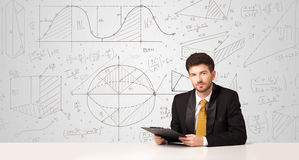 Businessman with business calculations background. Business man sitting at white table with hand drawn calculations background Stock Images