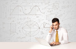 Businessman with business calculations background. Business man sitting at white table with hand drawn calculations background Stock Photos