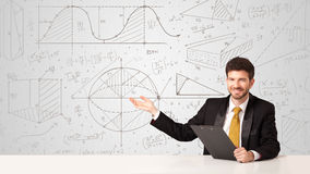 Businessman with business calculations background. Business man sitting at white table with hand drawn calculations background Royalty Free Stock Photo