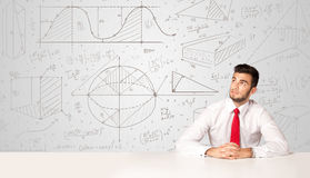 Businessman with business calculations background. Business man sitting at white table with hand drawn calculations background Royalty Free Stock Image