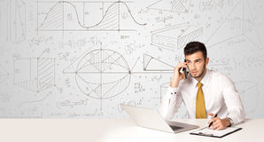 Businessman with business calculations background. Business man sitting at white table with hand drawn calculations background Stock Image
