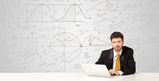 Businessman with business calculations background. Business man sitting at white table with hand drawn calculations background Stock Photography