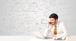 Businessman with business calculations background. Business man sitting at white table with hand drawn calculations background Royalty Free Stock Photos