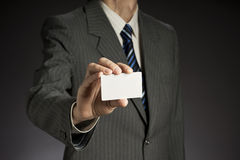 Businessman and business card. Businessman with jacket  stretches out a white business card, gray background Stock Photography