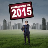 Businessman with business goals on the field. Young male entrepreneur holding a board on the meadow with a text of business goals for 2015 Stock Photography
