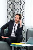 Businessman in business hotel is on phone Royalty Free Stock Photo