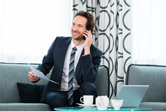 Businessman in business hotel is on phone Royalty Free Stock Photography