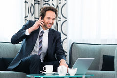 Businessman in business hotel is on phone Royalty Free Stock Images