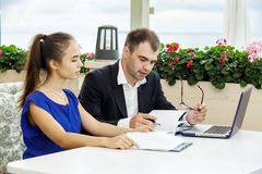 Businessman and business lady at a meeting. They are discussing the contract. The men in a suit and a white shirt. The women in a blue blouse Stock Photography