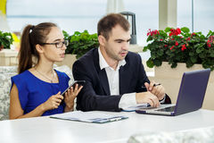 Businessman and business lady at a meeting. They are discussing the contract. The men in a suit and a white shirt. The women in a blue blouse and glasses Royalty Free Stock Image