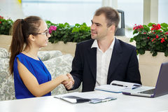 Businessman and business lady at a meeting. They are discussing the contract. Stock Photos