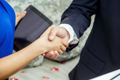 Businessman and business lady shake hands. The male in a suit and a white shirt. The woman in a blue blouse. A tablet in her second hand Stock Photography