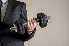 A businessman in business suit doing dumbbell biceps curl. Conceptual of determination and effort Royalty Free Stock Images