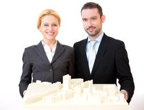Businessman and business woman presenting model Stock Photos