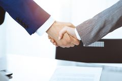 Businessman and business woman shaking hands to each other above signed contract. Success at negotiation and agreement. Businessman and business woman shaking royalty free stock image