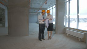 Businessman and business woman in suit, hard hat communicate, discuss blueprint, construction site. stock video