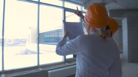 Businessman and business woman in suit, hard hat in a new unfinished office building communicate, discuss blueprint stock video footage