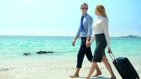 Businessman and business woman with a suitcase walking along the white sand beach on the island.  stock video footage