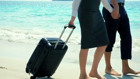 Businessman and business woman with a suitcase walking along the white sand beach on the island stock video