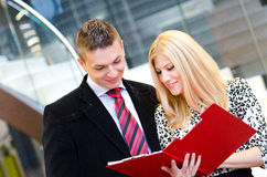 Businessman and business woman talking over documents Royalty Free Stock Image