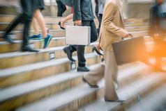 Businessman and Business woman up the stairs in a rush hour to w. Ork, city background Stock Photos