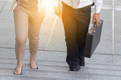 Businessman and Business woman walking up stairs with bags Royalty Free Stock Photos