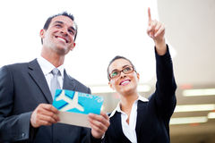 Businessman businesswoman airport. Young businessman and businesswoman looking at boarding information at airport Stock Photography